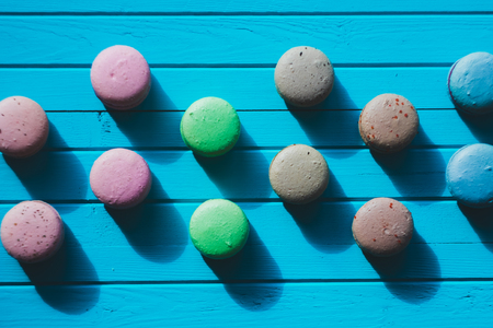 Multicolored macaroons or almond cookies lie on a wooden turquoise background in checkerboard pattern