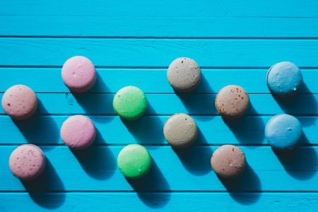 Multicolored macaroons or almond cookies lie on a wooden turquoise background in checkerboard pattern, copy space Stock Photo