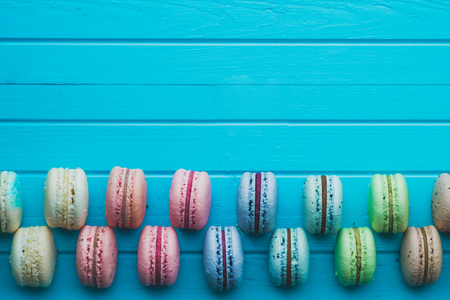 Cookies macaron or macaroons lie on a wooden turquoise background in checkerboard pattern, top view, copy space