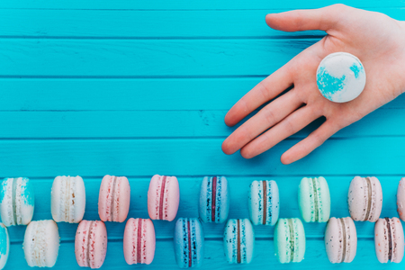 Macaroon or macaron lies in the hand of a girl on a wooden turquoise background. Gift from almond cookies, copy space