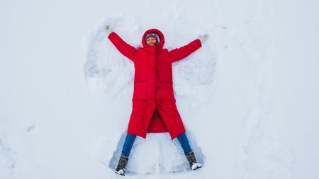 Junge Frau, die einen Schneeengel tut, Draufsicht Standard-Bild