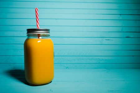 Orange juice in a jar with a reusable tubule on a turquoise background, copy space