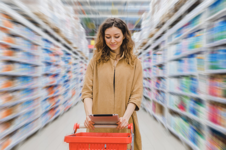 Young business woman with a grocery shopping cart looking into a tablet in a supermarket between shelves