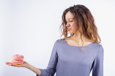 Young woman looks disgusted at donuts Banque d'images