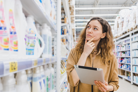 Business woman is thinking about shopping with a tablet selects household chemicals in a supermarket Banco de Imagens