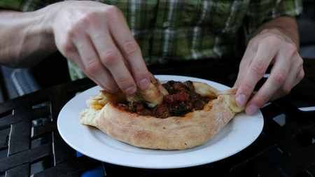 Man is eating a national Georgian dish - khachapuri, camera movement. The guy breaks off a piece of bread and dipping it in a vegetable filling close-up. Stock Photo