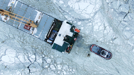 Aerial view. The big ship sails through the sea ice in the winter, close-up 版權商用圖片