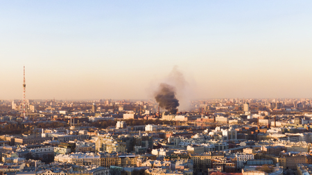 Black smoke rises above the horizon in the city, the building burns. Aerial view at sunset