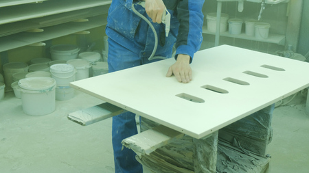 Worker dusting a sheet of plywood before painting. Factory for the production of wooden furniture