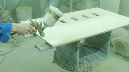 Worker paints a plywood sheet in a furniture factory. Manufacturing of wooden furniture