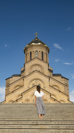 A girl in a long dress stands on the background of an old Christian temple