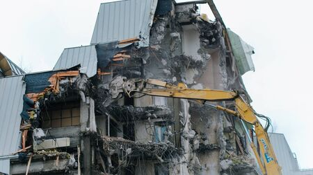 Timelapse excavator destroys a building. Falling pieces of concrete and rebar, demolition work. Reklamní fotografie