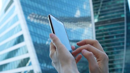 female hands are using a smartphone against the background of large glass business centers, close-up