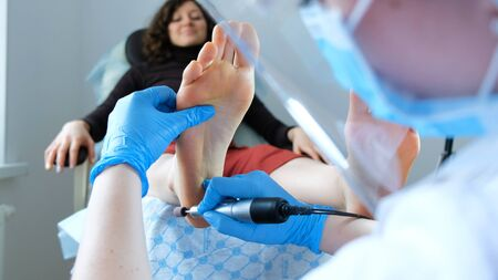 Medical hardware pedicure - pedicure master makes peeling on clients feet Reklamní fotografie