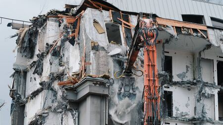 Excavator destroys the old building. Demolition work, pieces of concrete and reinforcement fall down