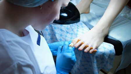 Pedicurist paints toenails at the client in the beauty parlor