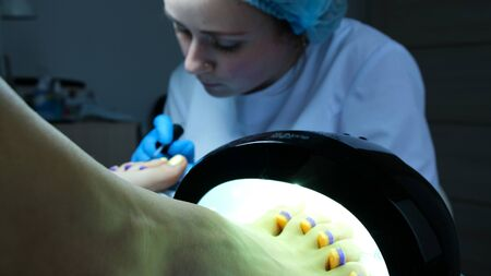 Toenails are dried in an ultraviolet lamp. Pedicure master paints nails with varnish on the background