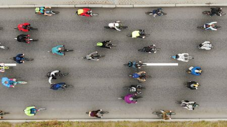 amateurs cyclists in colorful jackets participate in race and ride slowly along asphalt road vertical view