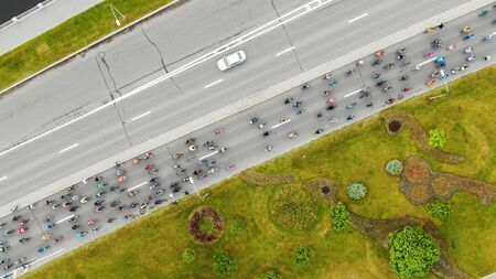 flycam shows flow of sportsmen riding bicycles along wide road past bright green garden and fast cars aerial view