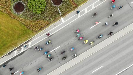 flying camera shows different cyclists in colorful jackets riding along new asphalt road past driving cars