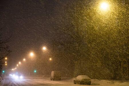 Evening street with lanterns during heavy snowfall, cars go towards and Shine headlights Stockfoto