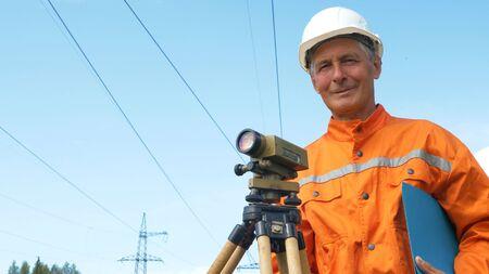 experienced surveyor stands near dumpy level holding folder
