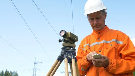 surveyor types on smartphone and looks through theodolite Stockfoto