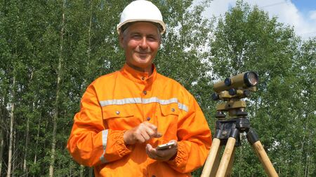 survey specialist looks through theodolite types and smiles