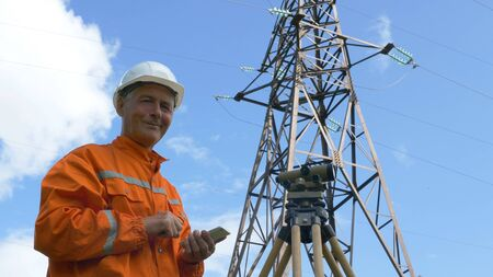 surveyor looks through theodolite and types on smartphone