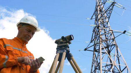 senior surveyor looks through level and types smiling