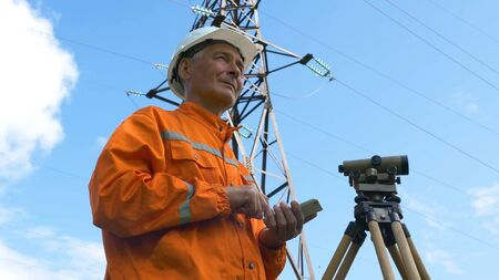 senior explorer types on modern phone at geodetic device