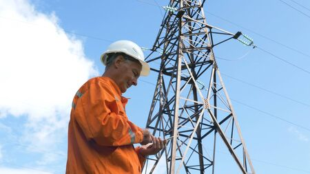 aged survey specialist types on smartphone under power lines