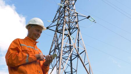 senior surveyor puts data in smartphone by power lines tower