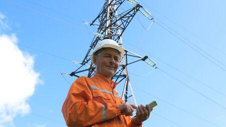 surveyor in jumpsuit and helmet smiles holding smartphone
