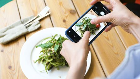 young woman focuses camera on green salad and makes photo Stockfoto