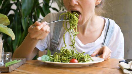 girl inputs fresh raw vegetable salad on silver fork