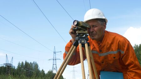 skilled aged surveyor looks through dumpy level and makes notes in blue folder under high-voltage power lines Banque d'images - 130668021