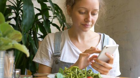 pretty lady types on modern smartphone and eats green salad Stockfoto