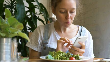 beautiful brunette types on smartphone and eats fresh salad