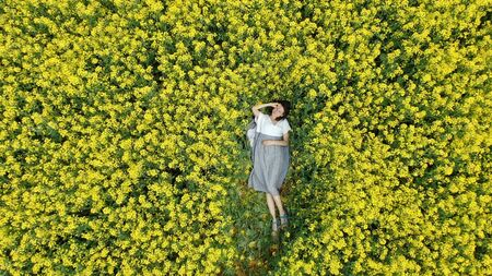 pretty girl rests on blooming rapeseed field zoom in Stockfoto