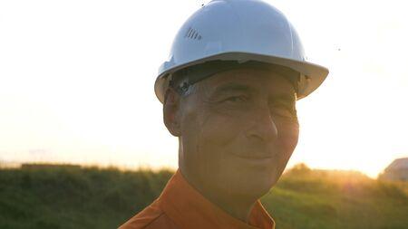 aged surveyor in orange jumpsuit types on modern smartphone Stockfoto