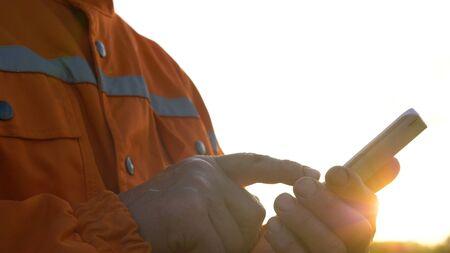 professional surveyor puts measurements to smartphone close