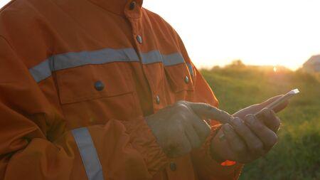 surveyor lit by sun types on modern smartphone and smiles Stockfoto