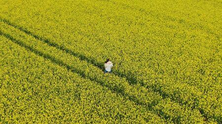 lady in summer dress hugs man in white shirt on field