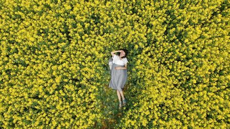 lady in white and grey summer dress lies on blooming field