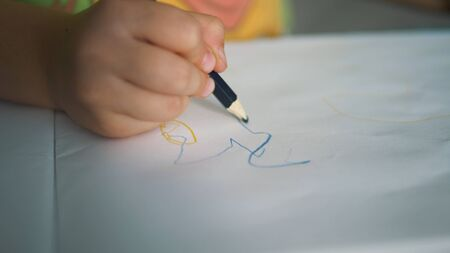 small child hand draws on white paper sheet with pencil