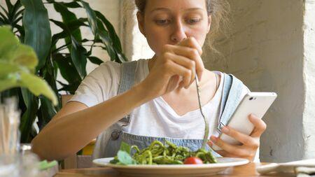 brunette student eats green fresh salad holding smartphone