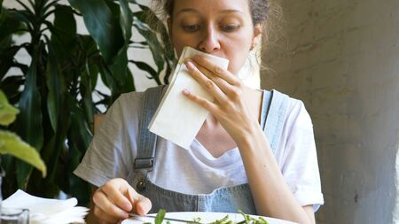 beautiful brunette eats green fresh salad and wipes mouth