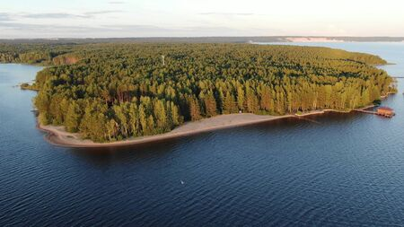 wide river bank with sandy beach against green forests