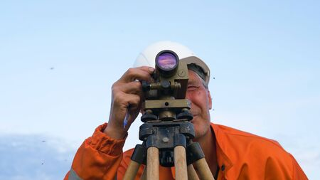 concentrated surveyor looks through theodolite and writes